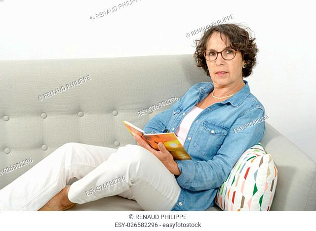 a woman of middle age reads, sitting on the sofa