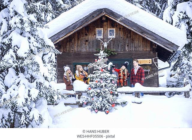 Austria, Altenmarkt-Zauchensee, friends decorating Christmas tree at wooden house