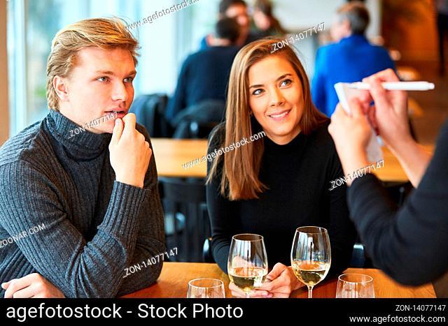 Junger Mann mit Freundin gibt seine Bestellung auf im Bistro oder Restaurant