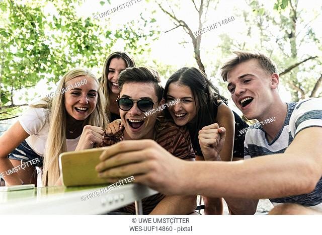 Group of happy friends looking at cell phone outdoors