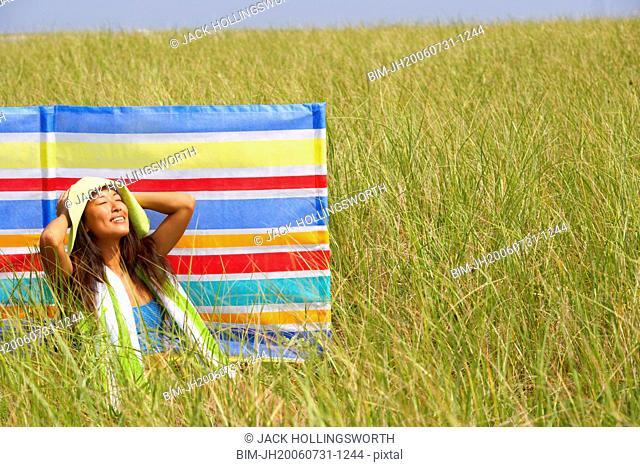 Asian woman sitting in field