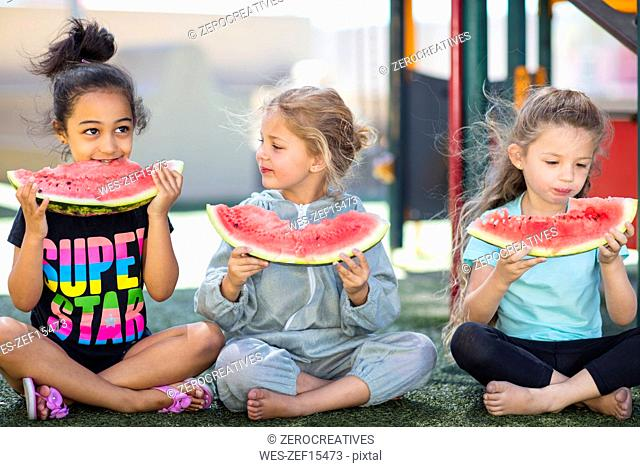 Three girls eating watermelons in kindergarten