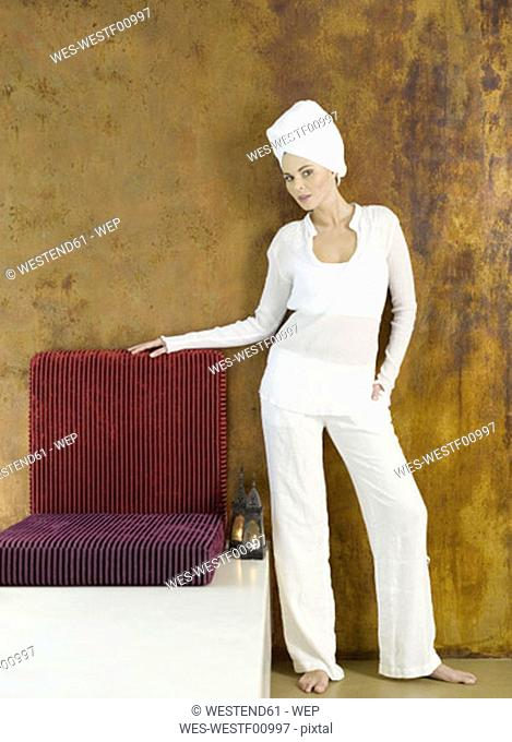Woman standing with head wrapped in towel