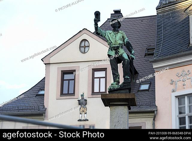 03 October 2020, Saxony, Schneeberg: At the market place there is the miner's fountain with the statue of a miner. The region around Schneeberg