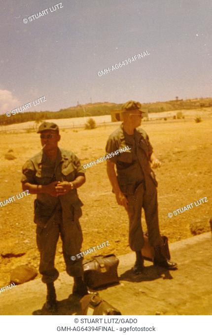 Staff Sergeant Melsan, Signal Corps, smoking a cigarette, and Sergeant First Class Anderson, Supply Corps, standing on the side of the road, bags by their feet