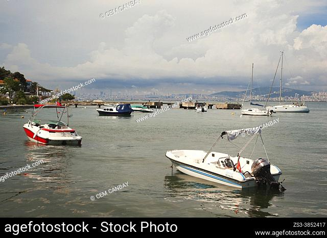 Boats near the pier in Burgazada, ancient Antigoni with the Istanbul landscape at the background, Prince Islands, Istanbul, Marmara Region, Turkey, Europe