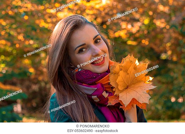 beautiful smiling girl in a scarf that keeps leaves close-up