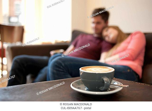 Young couple lounging on cafe sofa