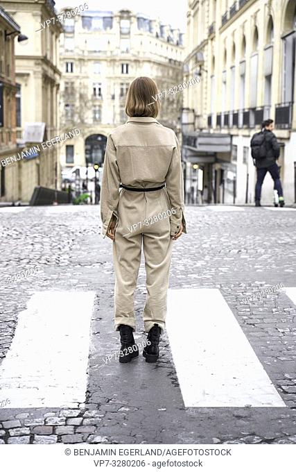 back of fashionable woman standing in street, in Paris, France