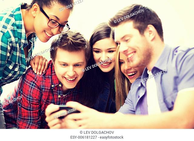 education and internet concept - smiling students looking at smartphone at school