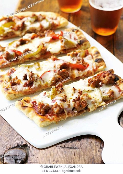 Pieces of pizza topped with sausage and peppers