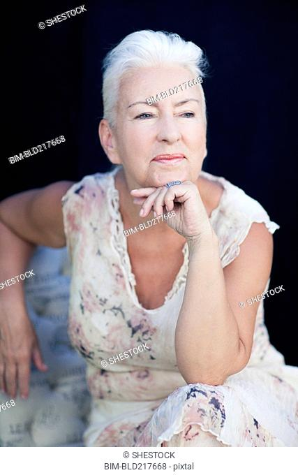 Caucasian woman resting chin in hand