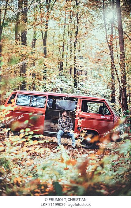 Man sitting in front of a VW Bus in the forest, Aalen, Ostalbkreis, Baden-Württemberg, germany, europe