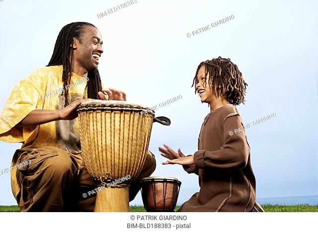 African father and son playing drums