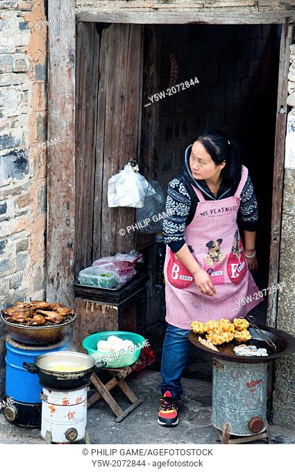 A woman cooking food for sale to tourists in Hongcun heritage village in Huizhou region, Anhui