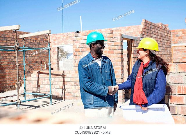 Woman and builder shaking hands on construction site
