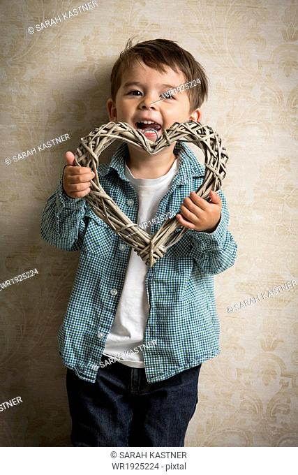 Little boy holding a wooden heart in his hand