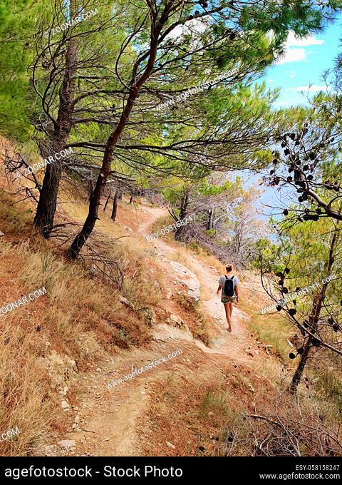 Young active feamle tourist wearing small backpack walking on coastal path among pine trees looking for remote cove to swim alone in peace on seaside in Croatia