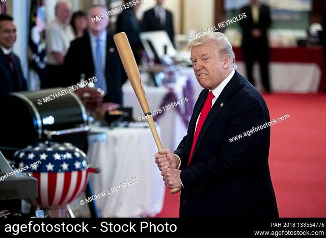 US President Donald J. Trump holds a baseball bat while participating in the 'Spirit of America Showcase', at the White House in Washington, DC, USA