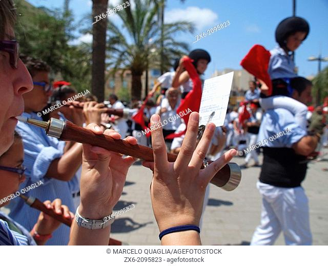 Human tower participators and cornet players ('els Castellers') at the end of their performance during Summer Festivities of Sant Carles de la Rapita Village