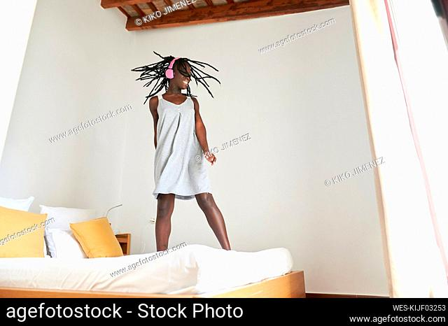 Young woman with headphones dancing on bed at home
