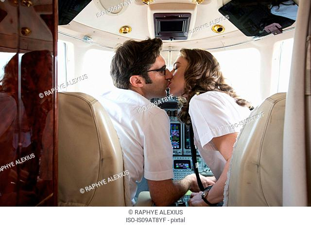 Rear view of male and female pilots kissing in cockpit of private jet