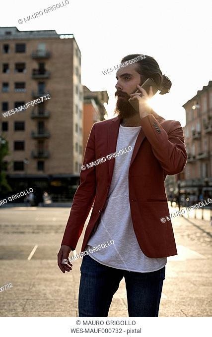 Young man with full beard telephoning with smartphone at backlight