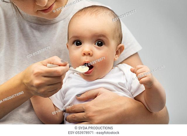 close up of mother with spoon feeding little baby