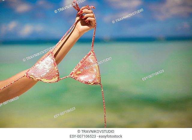 Woman's hand holding pink bra background the sea
