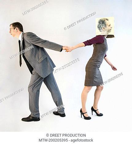 Businessman pulling businesswoman wearing mask
