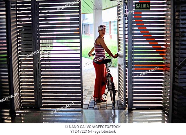 Young woman at home entrance, about to take a ride on her bicycle