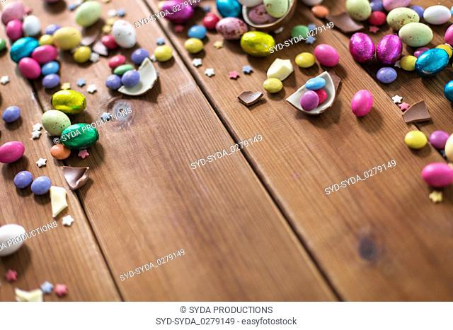chocolate eggs and candy drops on wooden table