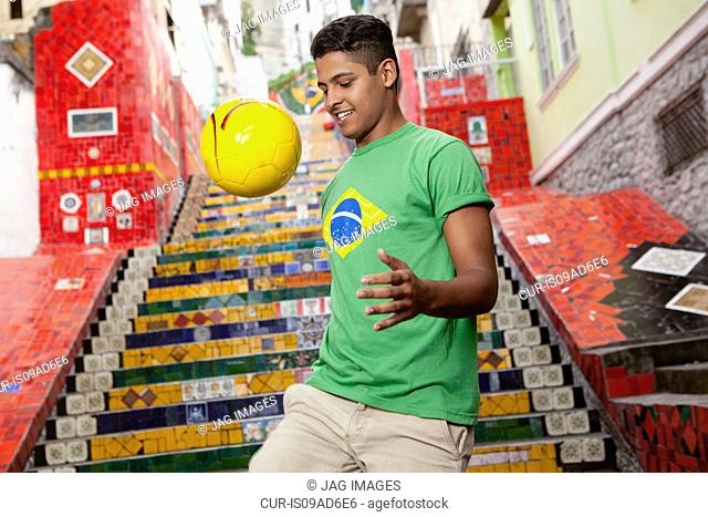 Young man wearing Brazil top doing keepy uppys in front of the Escadaria Selaron steps in Rio de Janiero, Brazil