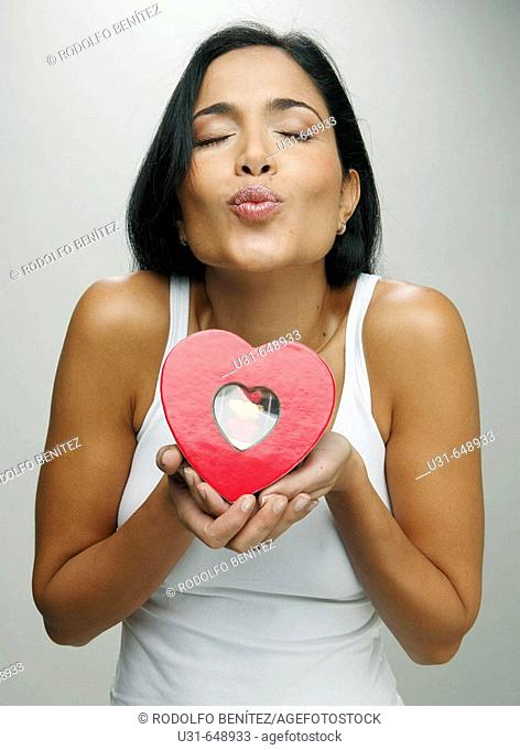 Latin girl blowing a kiss giving a valentine's chocolate heart