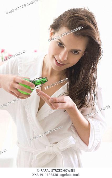 woman applying oil into hair endings