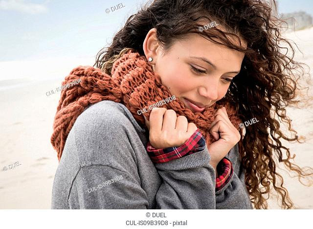 Portrait of young woman wrapped in scarf on windy beach, Western Cape, South Africa
