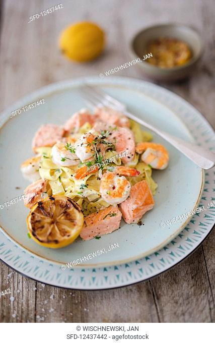Tagliatelle with prawns, salmon, sour cream and grilled lemons on a wooden table