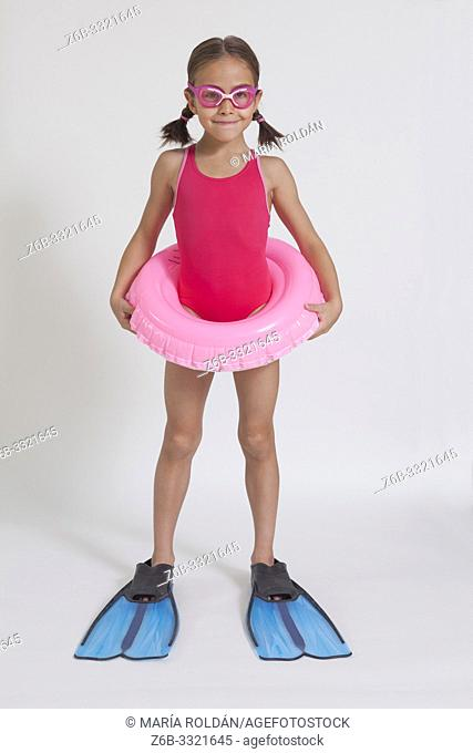 Studio full length portrait of a girl in swimsuit with a swim ring and flippers