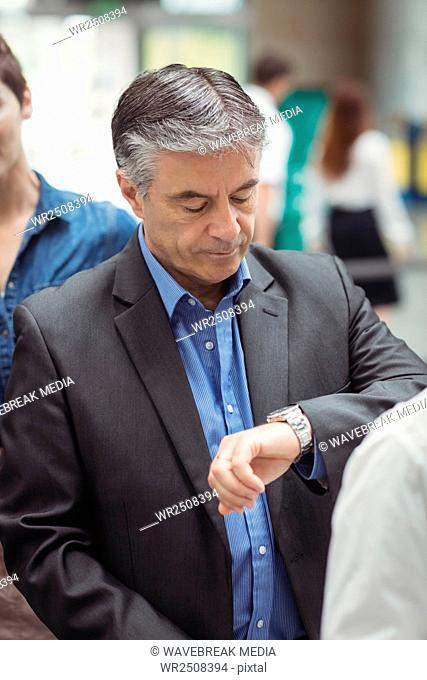 Business man checking time while standing in queue
