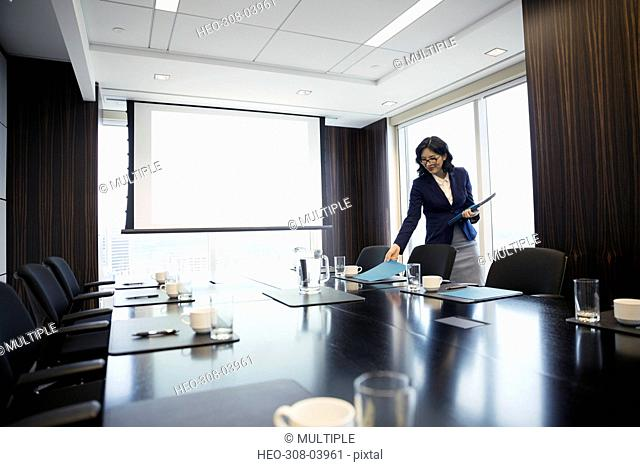 Businesswoman preparing for meeting placing folders on conference room table