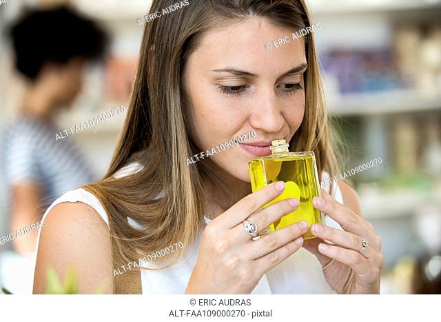 Young woman smelling perfume in shop