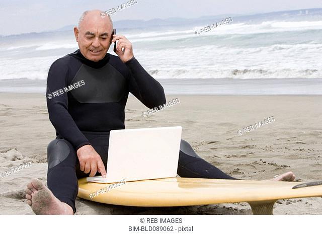 Senior Hispanic man sitting on surfboard using laptop and talking on cell phone