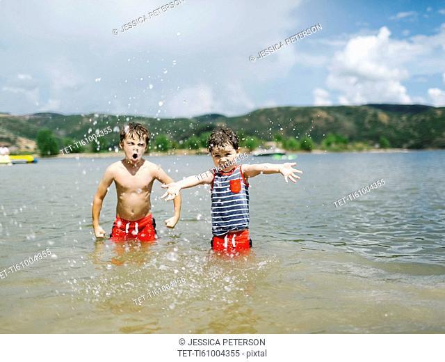 USA, Utah, Park City, Brothers (4-5, 6-7) playing in lake