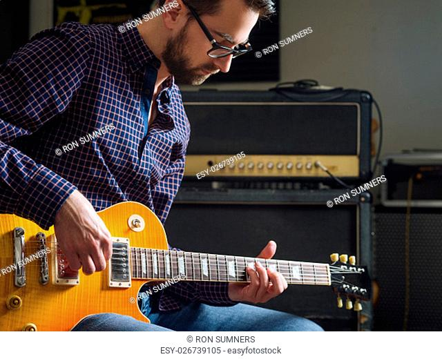 Photo of a man in his late 20's sitting in a studio playing his electric guitar