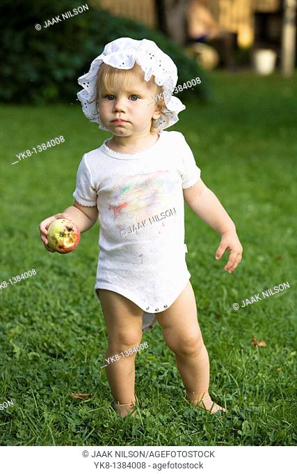 One Year Old Baby Girl Standing Outside with Apple in Hand