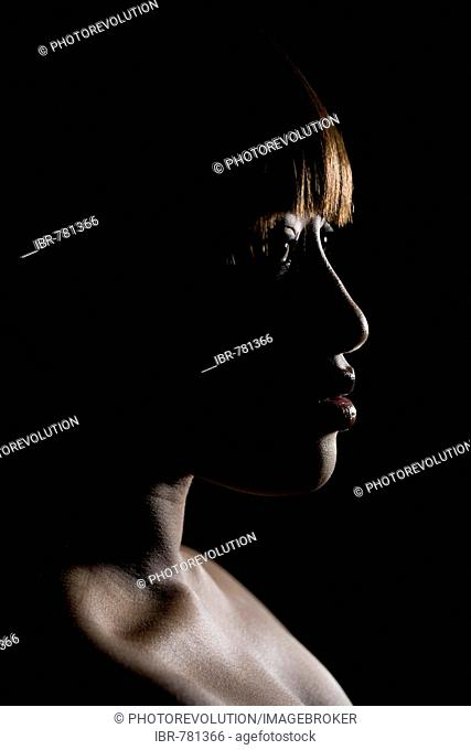 Silhouette of a young, dark-skinned woman's head, profile