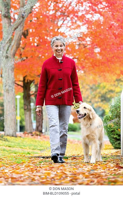Mixed race woman walking dog