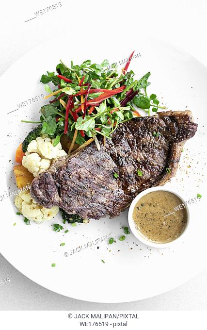 premium beef steak with steamed vegetables and mushroom sauce gourmet meal on white plate