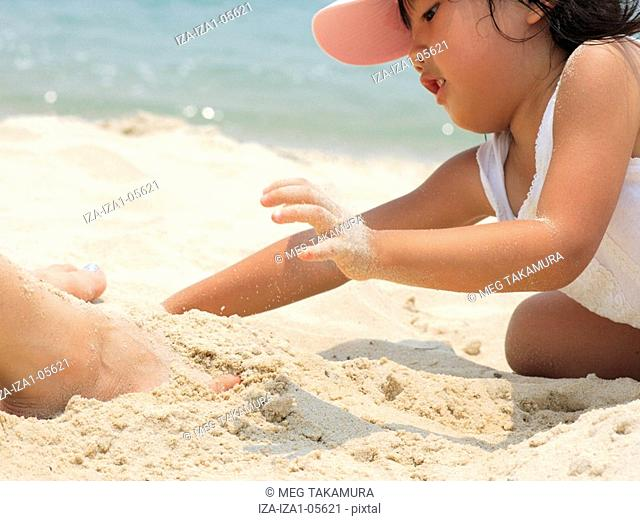 Side profile of a girl playing with sand on the beach