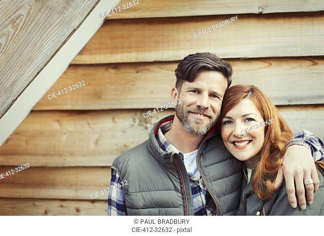 Portrait smiling couple hugging outside cabin